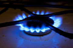 Old gas cooker. Dirty old gas cooker with blue flame stock photography