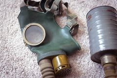 Old gas mask with filter. Gas mask with filter on a floor. Old anti-pollution mask indoor. Vintage gas mask using during chemical hazard. Concept of stock photo