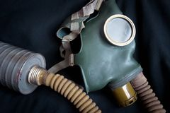 Old gas mask with filter. Gas mask with filter on a dark background. Old anti-pollution mask indoor. Vintage gas mask using during chemical hazard. Concept of stock image