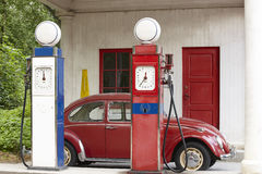 Old gas petrol station. Petrol pump and antique beetle car Stock Photo