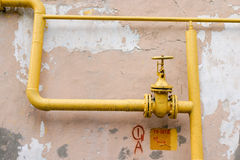 Old gas pipe. Old yellow gas pipe over dilapidated wall Stock Image