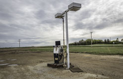 Old gas pump sitting under broken light stand. Stock Images