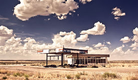 Old gas station in ghost town along the route 66. At border of the desert Stock Photos