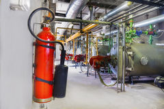 Old gas steel boilers and fire extinguisher. On a wall established in old boiler-house royalty free stock photography
