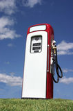 Old Gasoline Pump. A vintage antique Gasoline fuel pump sitting on a grassy hill against the blue sky Stock Photo