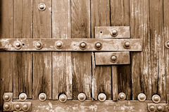 Old gate. Lower part of an old heavy wooden door in ancient house. Sepia Stock Images