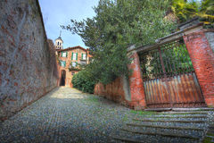 Old gate and narrow paved street in Saluzzo. Royalty Free Stock Photo
