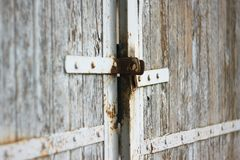 Old gate with rusty latch and painted white stock photography