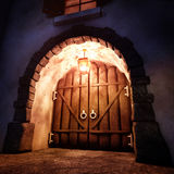Old Gate. A wooden old gate from mediaeval era lit by a lamp under moon light. Arch adorned with block stones Stock Photo