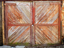 Old gates, collected from slanting slats, with peeling paint. Ol. Old wooden gate of a barn with a padlock. Old gates, collected from slanting slats, with Royalty Free Stock Images
