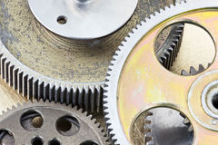 Old gears and other details of machines on brass background Stock Photos