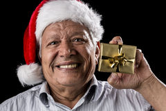 Old Gentleman With Red Hat Offering Golden Gift. Aged, happy man is cracking a smile while holding up a small wrapped golden present in his left hand. He is Royalty Free Stock Photos