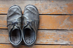 Old genuine leather shoes on a wooden background Stock Photo