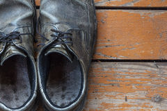 Old genuine leather shoes on a wooden background Stock Photos