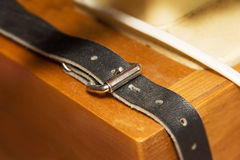 Old Genuine leather strap. On wood background Royalty Free Stock Photography
