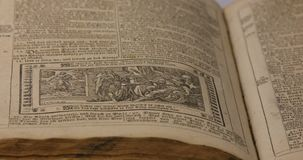 Old German Bible from 1747 with text and illustration. Pan across the timeworn pages of an old German Bible, from illustration to text, dating from 1747 AD stock footage