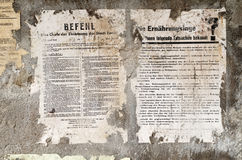 Old german damaged poster newspaper news on a wall. Old german damaged depressing poster newspaper news on a wall Stock Photos