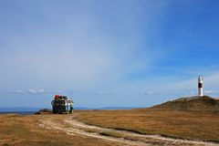 Old german vintage campervan camping at the lighthouse and the bay of Porvernir, Chile. Old german vintage campervan camping at the lighthouse and the bay of royalty free stock image