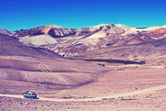 Old german vintage campervan cruising road in the andean mountains, Nashville retro vintage photo filter effect, warm. Old german vintage campervan cruising an Stock Images