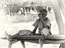 An old from Ghana sits the curious way on a woode Stock Image