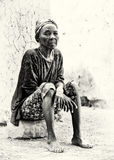 Old Ghanaian lady sits on the stone Royalty Free Stock Photo