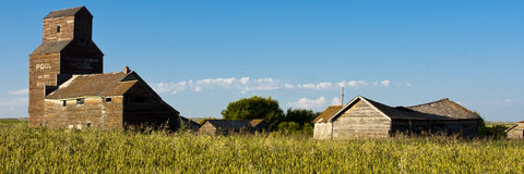 Old Ghost Town. Vintage old-fashioned buildings abandoned in an old ghost town beyond a rural field Royalty Free Stock Image