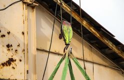 Old girder crane with large iron hook lifts  heavy load on  slings stock photography