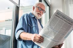 Old glad pensioner reading newspaper near window. Curious publication. Portrait of senior interested man holding paper while relaxing near window Royalty Free Stock Photos