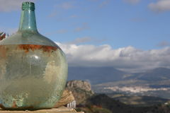 Old Glass Bottle. Old and round glass bottle with mountainous Andalusian white village in the background Stock Photography
