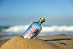 Old glass bottle with 500 euro banknote inside, sand of the beach Royalty Free Stock Photos
