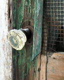 Old glass door knob covered with snow on a dilapidated old wooden screen door. Rusty screen, green patina on wood, splitting wood royalty free stock photography