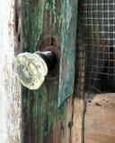 Old glass door knob with snow on dilapidated screen door. Green patina, broken screen, wooden door Stock Image