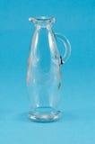 Old glass jug jar pitcher handle on blue Stock Photo