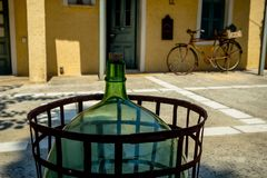 An Old Glass Wine Bottle in the Courtyard with an Old Bicycle Wheel. A Quiet Place on a Paved Courtyard Somewhere in Greece stock photos