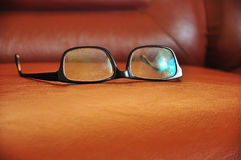 Old glasses. On the brown sofa royalty free stock photo