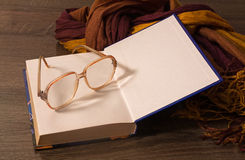 Old glasses lying on the book. Grandma glasses and scarf lying on the open book Stock Photography