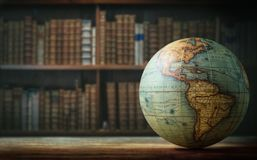 Old globe on bookshelf background. Selective focus. Retro style. Science, education, travel, vintage background. History and geography team royalty free stock photography