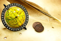 Old globe, feather and  coins. Antique globe, feather and old coins on grunge background Stock Image