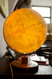 Retro globe. Old globus glowing in yellow light in natural lit room Royalty Free Stock Photos