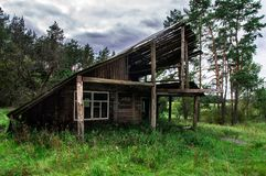 Old gloomy abandoned wooden house in the forest royalty free stock photo