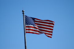 Old glory. Shot of american flag waving in the breeze with a clear blue sky behind it stock photos