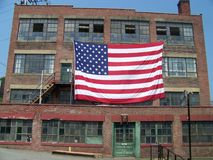 Old Glory. An old brick machine shop proudly displays the American flag Royalty Free Stock Photo