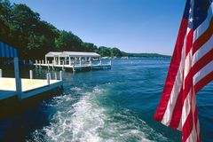 Old glory Flag and boat wake. View of old glory flag and wake from speedboat on Lake Geneva Wisconsin united states of america with Flag on stern with docks royalty free stock photos