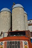 Old GMC truck parked in front of stave silos Stock Photos