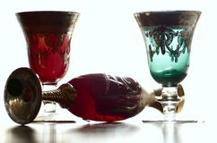 Old goblets. Green and red old crystal goblets in transparency Stock Photos
