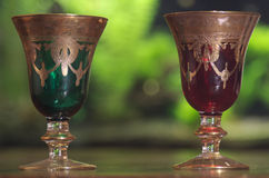 Old goblets. Red and green goblets in transparency Royalty Free Stock Photography