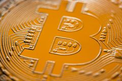 Old Gold Color of Bitcoin. Bitcoin currency DOF on blue glass background. Gold metal currency symbol macro photo closeup royalty free stock image