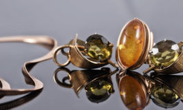 Old gold earrings with green stones and a ring with amber Stock Images