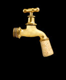 Old gold faucet closed with cork on black Stock Images