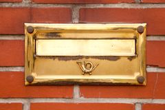 Old gold post box on brick wall. Old gold post box located on brick wall Royalty Free Stock Image